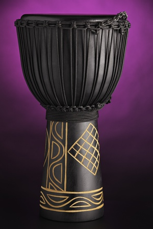 A black African djembe drum Isolated against a purple spotlight background photo