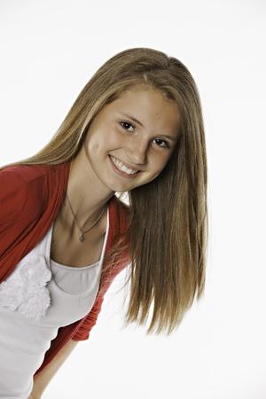 A largo cabello castaño adolescente femenina que es todo sonrisas sobre un fondo blanco. Foto de archivo - 10034125