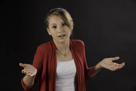cute attitude: A teenage female girl asking a question against a black background.
