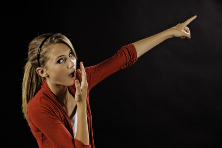 A surprised teenage female girl pointing off into the distance  against a black background. Stock Photo - 10034132