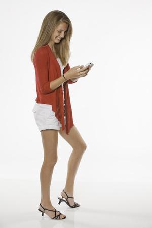 白い背景に対して隔離される電話での幸せなかなり 10 代女性女の子テキスト メッセージ。 写真素材