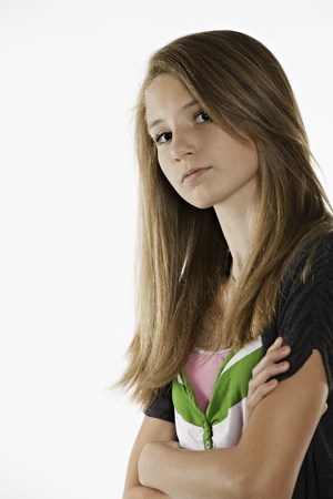 A pretty teenage female girl leaning against a wall isolated on white Stock Photo