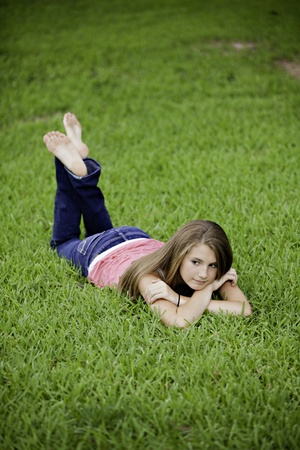 A pretty teenage female girl laying face down on green grass looking thoughtful.