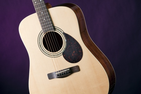 An acoustic guitar music instrument isolated against a dark spotlight purple background. photo