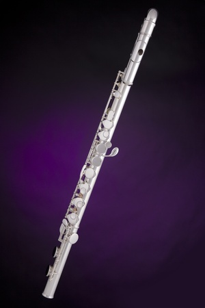 A professional silver alto flute woodwind instrument isolated against a spotlight purple background. photo