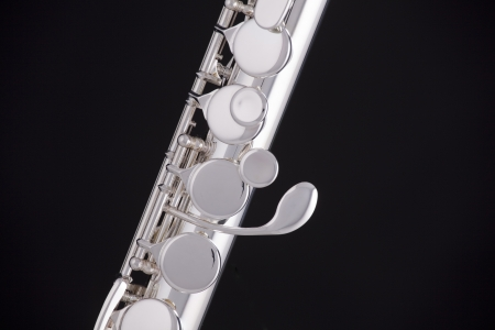 flute key: A professional silver alto flute woodwind instrument isolated against a black background.