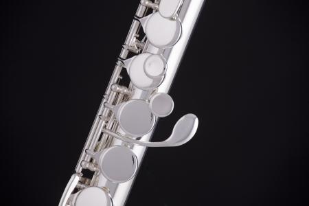 flauta: Un instrumento de viento flauta plata profesional aislado contra un fondo negro.