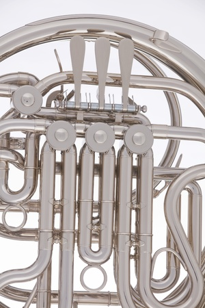 A silver French horn isolated against a white background in the vertical format. photo