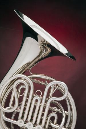 symphony: A silver French horn isolated against a spotlight red background in the vertical format. Stock Photo