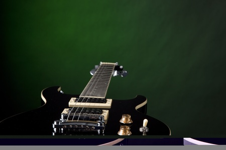 fretboard: A jet black electric guitar isolated against a spotlight green background with copy space.