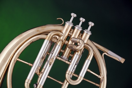 french horn: An antique brass peckhorn or French horn isolated against a spotlight green background.