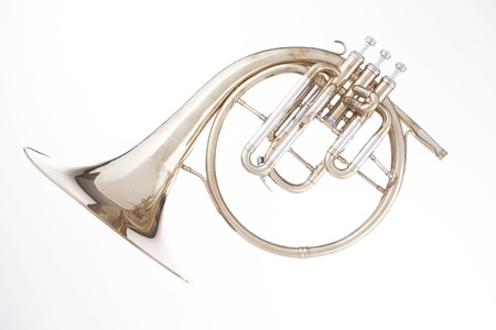 An antique brass peckhorn or French horn isolated against a white background. Stock Photo