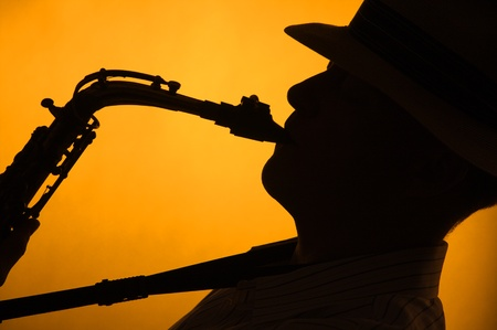 A saxophone player with a hat in silhouette against a stage light gold or yellow background in the horizontal format with copy space.