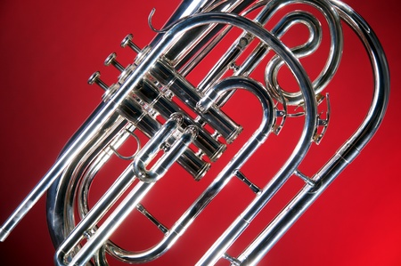 horizontal format horizontal: A silver marching French horn isolated on a red background in the horizontal format with copy space. Stock Photo