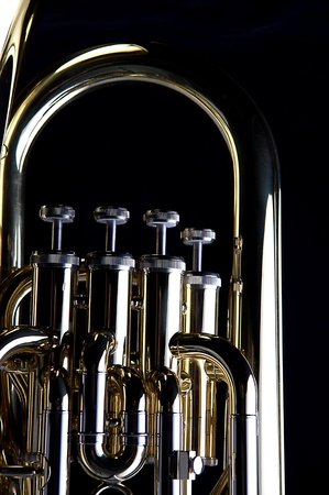 vertical format: A brass gold bass tuba euphonium isolated against a black background in the vertical format.