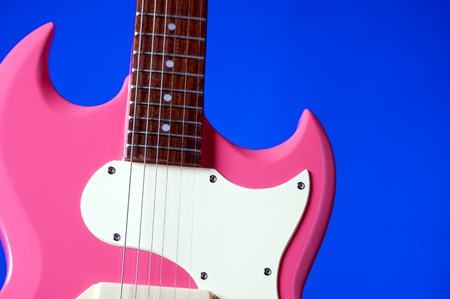 frets: A pink ladies electric guitar isolated against a blue background in the horizontal format with copy space.