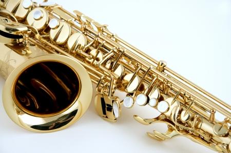 saxofon: Un saxofón aislado contra un fondo blanco en el formato horizontal con espacio de copia.