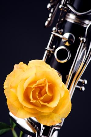 clarinete: Una Rosa amarilla montado en clarinete soprano aislado contra un fondo negro en el formato vertical.