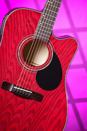 frets: A red acoustic electric guitar on a pink background in the vertical format.