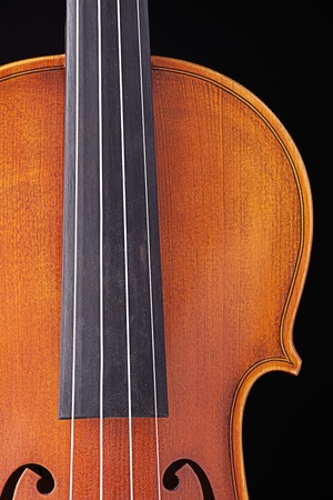 violins: A professional violin viola isolated against a black background. Stock Photo
