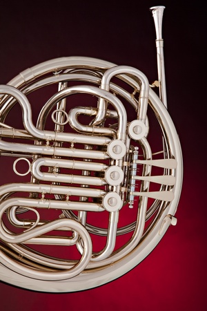french horn: A silver French horn isolated against a spotlight red background in vertical format.
