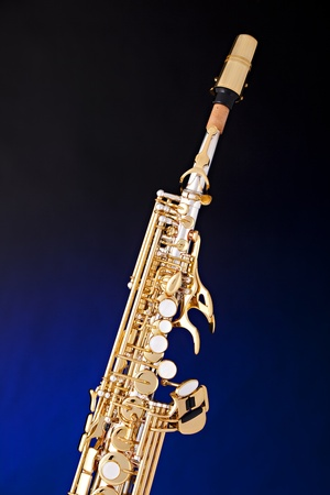 A gold and silver soprano saxophone isolated against a spotlight blue background. photo