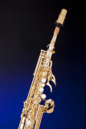 soprano saxophone: Un saxof�n soprano de oro y plata aislado contra un fondo azul, centro de atenci�n.
