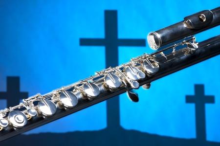 silver flute: A bass flute shot against a three Christian cross blue background.