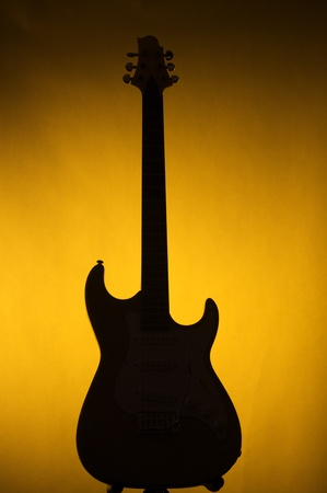 An electric guitar in silhouette against a gold or yellow background in the vertical forma.