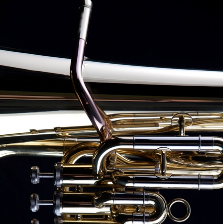 A gold brass tuba euphonium isolated on a black background in the square format with copy space.