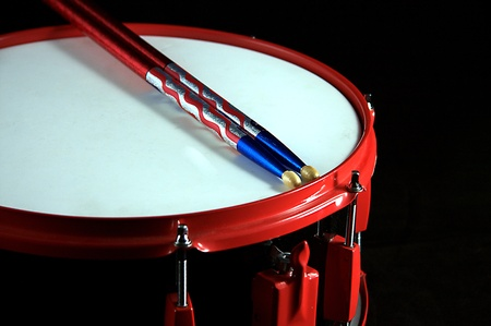 A red and black colored snare drum with flag colored sticks against a black background in the horizontal format.