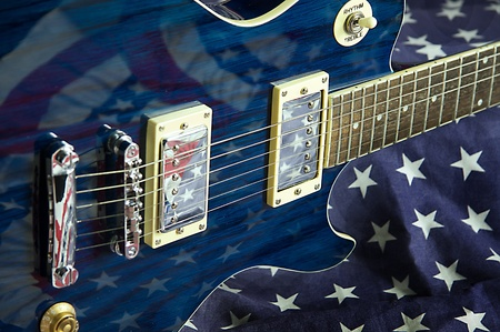 A blue wood electric guitar shot on an American flag background in the horizontal format.