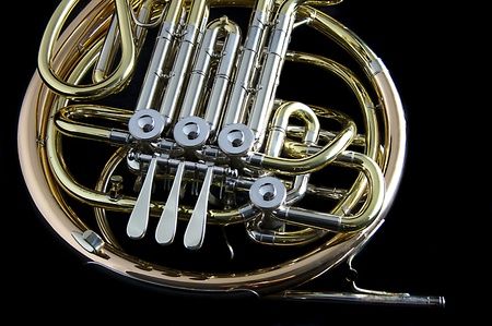 french horn: A gold brass French Horn against a black background in the horizontal format with copy space.