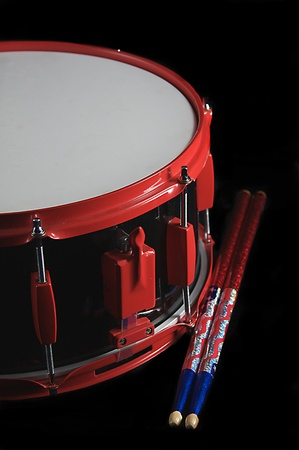 A red and black colored snare drum with flag colored sticks isolated against a black background in the vertical format.