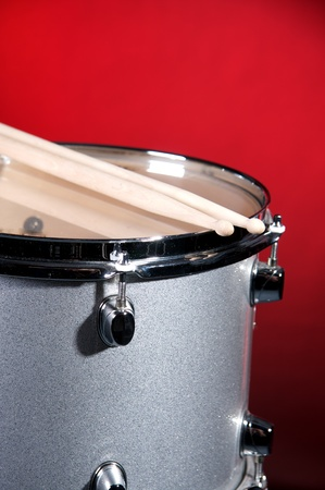 drum sticks: A silver sparkle tom drum with sticks isolated against a red background in the vertical format.