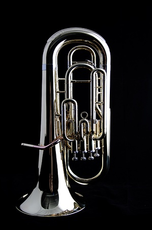 A brass gold bass tuba euphonium against a black background in the vertical format with copy space.
