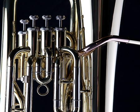 A brass gold bass tuba euphonium isolated against a black background in the horizontal format.