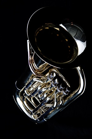 A complete brass gold bass tuba euphonium against a black background in the vertical format with copy space. Stock Photo