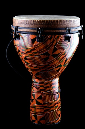 A complete orange African or Latin Djembe conga drum isolated on black background in the vertical format. photo