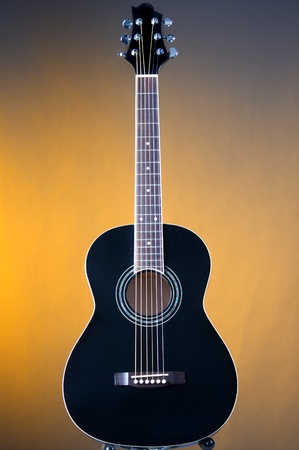 A black acoustic guitar isolated against a gold or yellow background in the vertical format. Stock fotó