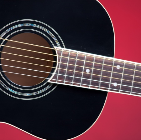 frets: A black acoustic guitar isolated against a gold or red background in the square format with copy space.