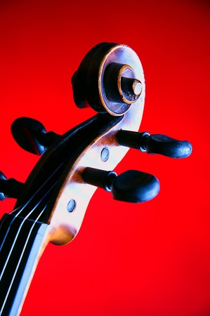 A violin viola scroll isolated on a red background in the vertical format. photo