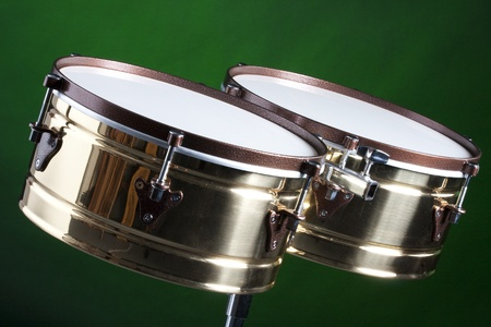 percussion: A set of brass and copper timbales isolated on a green background in the horizontal format.