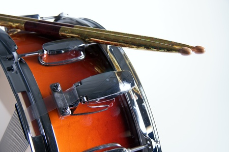 horizontal format horizontal: A red fade color snare drum with sticks isolated against a white background in the horizontal format.