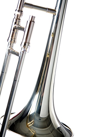 brass band: A silver trombone isolated against a white background in  the vertical format with copy space. Stock Photo