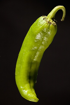 green peppers: A large green chili pepper isolated against a clean black background.