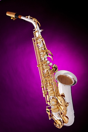 A silver and gold alto saxophone isolated against a spotlight pink background in the vertical format. Stock Photo