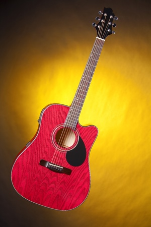 frets: A red acoustic guitar isolated against a spotlight yellow background in the vertical format.
