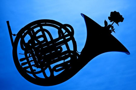 french horn: A French horn and rose flower in silhouette isolated against a blue background. Stock Photo