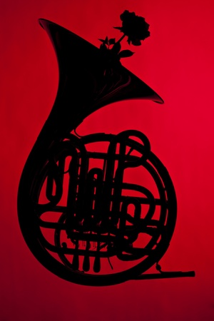 A French horn silhouette with a flower isolated against a red background. photo